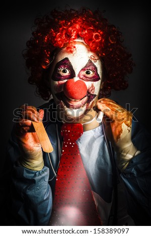 Scary medical clown doctor about to perform oral examination on victim with hand light and tongue depressor. Madness in medical torture - stock photo