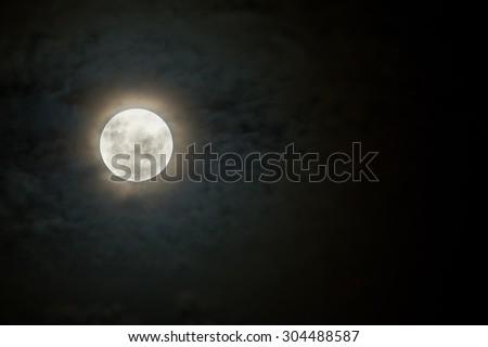 Scary moon on a dark and cloudy night with halo - stock photo