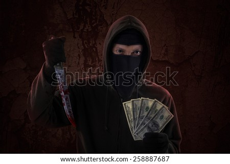 Scary murderer showing bloody knife while holding money cash - stock photo