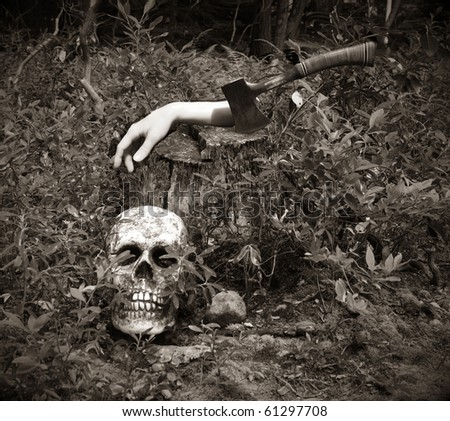scary scene of a dismembered human hand on a stump with a hatchet and skull - stock photo