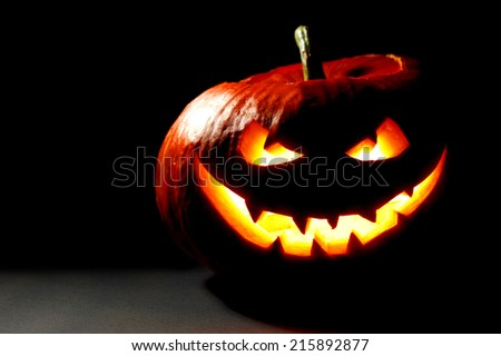 Scary smiling Halloween pumpkin on dark background - stock photo