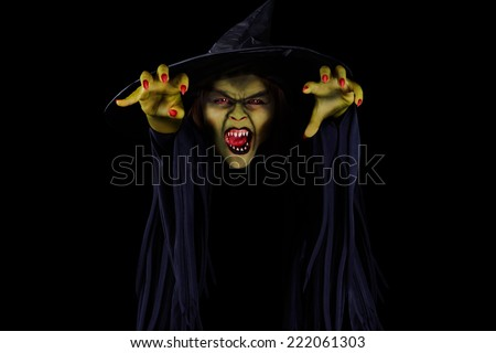Scary wicked witch trying to catch viewer, Halloween concept - stock photo