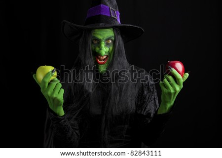 Scary witch and her poisonous apples, black background. - stock photo