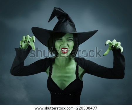 Scary witch with green skin performs magic on dark background. Halloween, horror theme. - stock photo