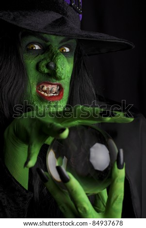 Scary witch with her crystal ball, black background. - stock photo