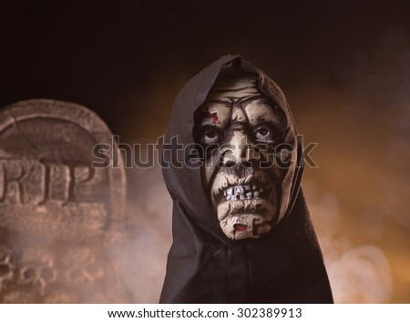 Scary zombie halloween prop with a tombstone and smoky background - stock photo