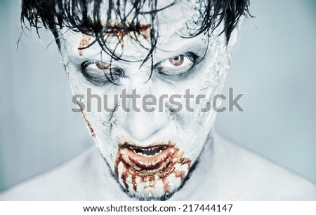 Scary zombie man in blood on white background, Halloween or horror theme - stock photo