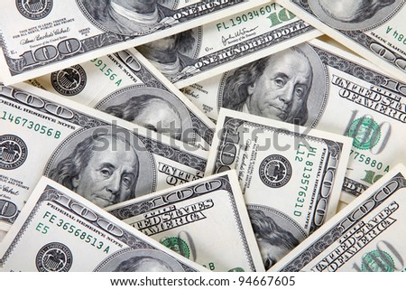 scattered a lot of money bills by hundreds of dollars - stock photo