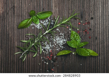 Scattered fresh basil and rosemary, sea salt and dry peppercorns - stock photo