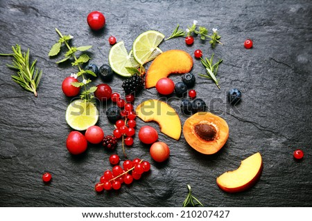Scattered fresh fruit and berries with cranberries, blackberries, redcurrants, lemon, peach, blueberries, rosemary and herbs on a textured slate background - stock photo