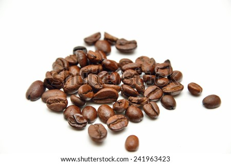 scattered glossy coffee beans on white background - stock photo
