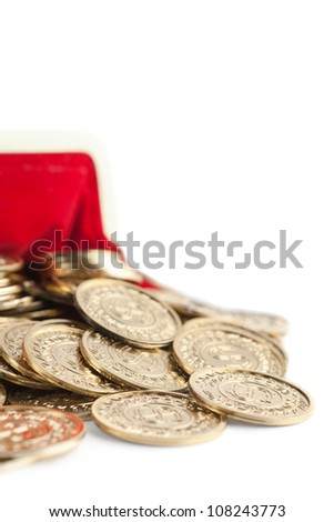 Scattered gold coins are in hot red partly viewed purse, isolated on white. A great number of coins symbolize wealth, richness, income and profit. Close up shot. - stock photo