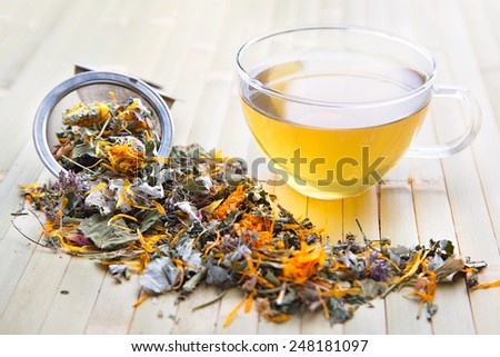 Scattered herb on bamboo in ball strainer and transparent cup with yellow herbal tea - stock photo