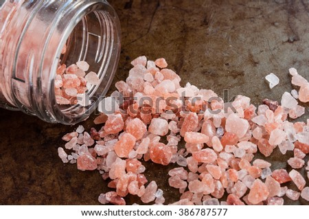 Scattered Himalayan pink salt crystals from glass bottle on rusty metal background - stock photo