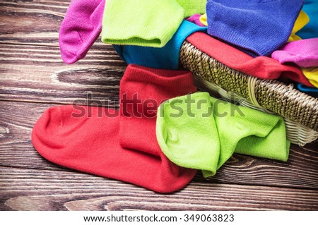 scattered multi-colored socks and laundry basket on a wooden background. - stock photo