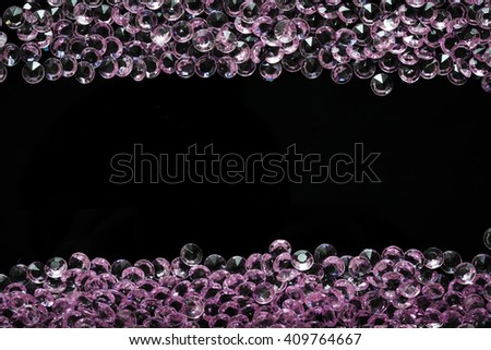 Scattered pink crystals arranged in two horizontal bands with copyspace for text in the middle - stock photo