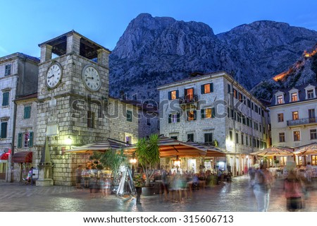 Scene in the medieval town of Kotor, Montenegro at twilight, featuring the Square of Arm and the clock tower near the Maritime entrance gate. - stock photo