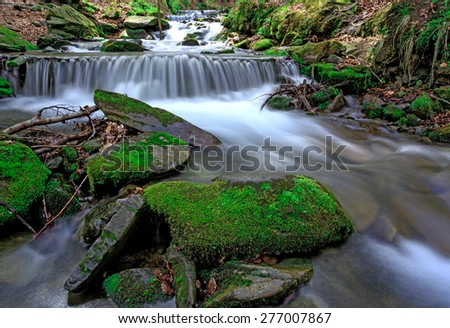 Scene with green moss stones in waterfall on mountain river - stock photo