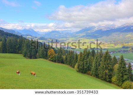 Scenery of an alpine ranch with village Ellmau in the valley and a mountain range in the distant background ~ Beautiful autumn landscape of Wilder Kaiser Mountains in Tirol, Austria, Europe - stock photo