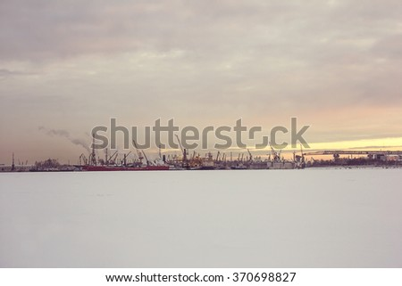 scenery of seaport in winter time with cranes, ships - stock photo