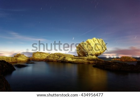 Scenery of the famous Fist (Punch) Rock by a beautiful beach on northern coast of Taiwan, with peaceful sea water illuminated by the morning twilight and star trails in the dawning sky (long exposure) - stock photo