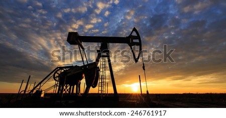 Scenery with oil and gas well pump and dramatic sunset - stock photo