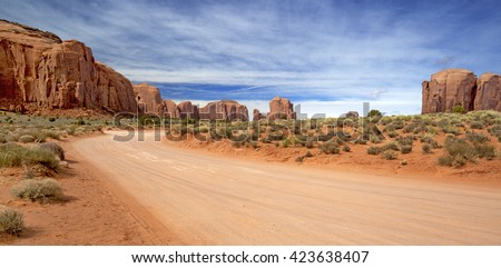scenic and empty dirt road in monument valley - stock photo