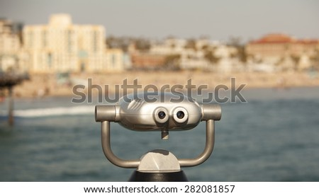 Scenic beach view from binoculars mounted on a pier. - stock photo