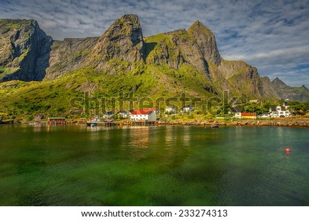 Scenic fjord on Lofoten islands with typical red fishing hut and towering mountain peaks - stock photo