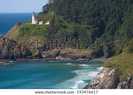Scenic headland cliffs rise in the foreground at Heceta Head lighthouse on Oregon's central coast. A popular landmark and tourist attraction. - stock photo