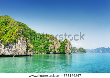 Scenic karst isles on blue sky background in the Ha Long Bay (Descending Dragon Bay) at the Gulf of Tonkin of the South China Sea, Vietnam. The Halong Bay is a popular tourist destination of Asia. - stock photo