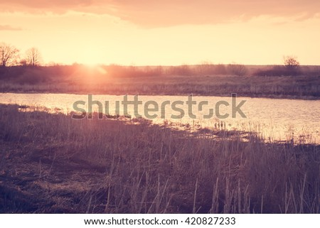 Scenic landscape during sunrise at river bank in rural field. Grass and sky  illuminate with golden color of the rising sun. Two banks of river are visible on picture - stock photo