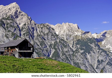 Scenic landscape of Karwendel mountain range in Austria with wooden hut and meadow - stock photo