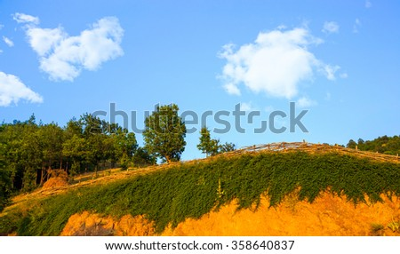 Scenic Landscape Profile View of Hilltop Covered with Vegetation and Topped by Fence and Green Forest Trees on Sunny Day with Blue Sky with Puffy White Clouds - stock photo