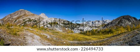 Scenic Landscapes of a high mountain valley and golden Larch Trees, Burstall Pass area of Kananaskis Country Alberta Canada on a sunny Autumn afternoon. - stock photo