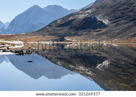 Scenic mountain autumn landscape with a lake, mountains reflecting in the lake, with snow and ice on the shore on a sunny day - stock photo