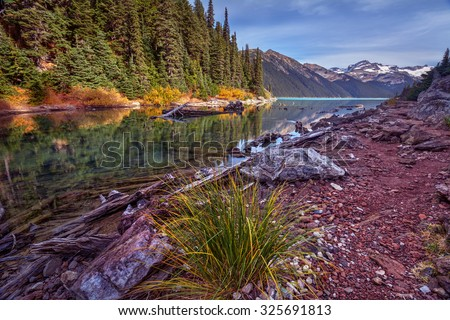 Scenic mountain lake with fall colors on a pine tree covered shore - stock photo