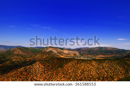 Scenic mountain landscape - the village, surrounded by low mountains, covered with juniper, on a clear sunny summer day, Crimea - stock photo