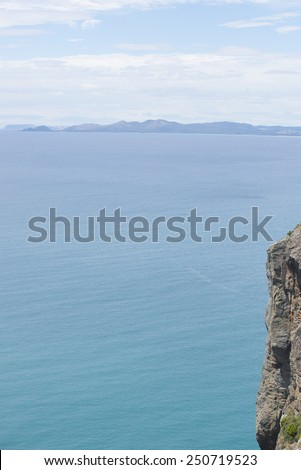 Scenic ocean panorama view from cliff lookout in Tasmania Australia at Bass Strait, with mountains as blurred background at horizon and copy space. - stock photo