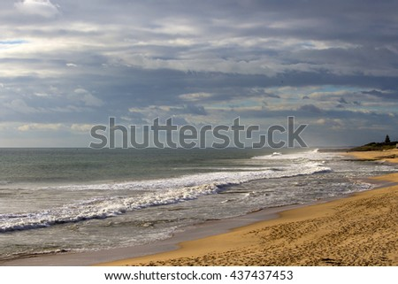 Scenic Panorama of Ocean Beach Bunbury Western Australia on a stormy cloudy  cold   late afternoon in early winter  with waves breaking  on the wet sandy shore. - stock photo