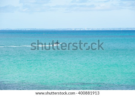 Scenic panorama view from Rottnest Island, Western Australia, to coast across Indian Ocean, with yacht and skyscrapers of Perth city in background. - stock photo