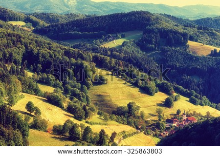 Scenic panoramic landscape: summer mountain valley with forests, fields and old church in Germany, St. Ulrich, Black Forest - stock photo
