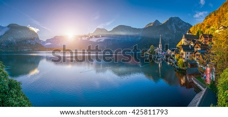 Scenic panoramic picture-postcard view of famous Hallstatt mountain village with Hallstatter See in the Austrian Alps at sunrise in beautiful golden morning light in fall, Salzkammergut, Austria - stock photo