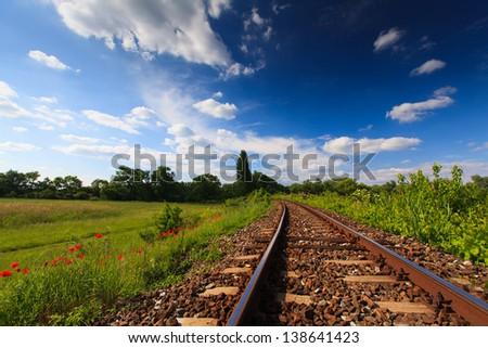 Scenic railroad in rural area in summer - stock photo