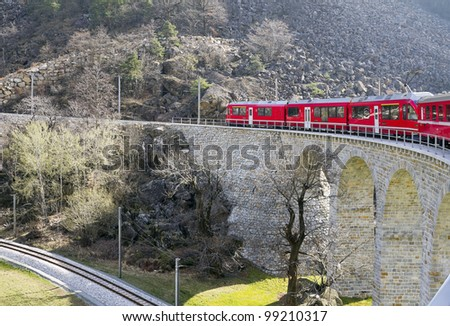 Scenic Railroad Pictures of Alps Train on viaduct - stock photo