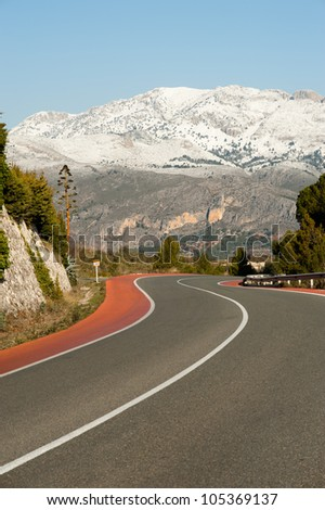 Scenic road bending amidst snowcaped mountains - stock photo