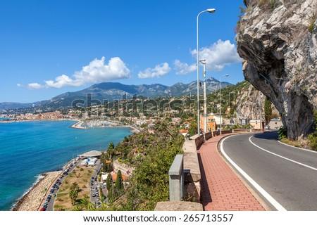 Scenic road under blue sky along Mediterranean sea coastline on French-Italian border. - stock photo