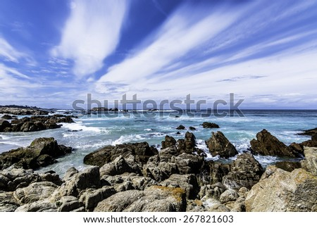 Scenic rocky coastline along the historic 17 Mile Drive in Pebble Beach California. Blue sky and sea, with white clouds. - stock photo