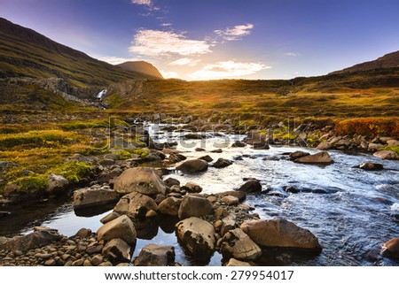 Scenic stream and waterfall in the valley by Seydisfjordur fjord at sunset - stock photo