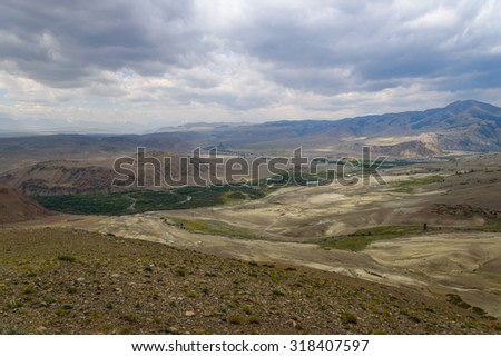 Scenic top view on the mountains, the valley between the mountains, winding river, forest and mountain slopes covered with sparse vegetation on a cloudy summer day - stock photo